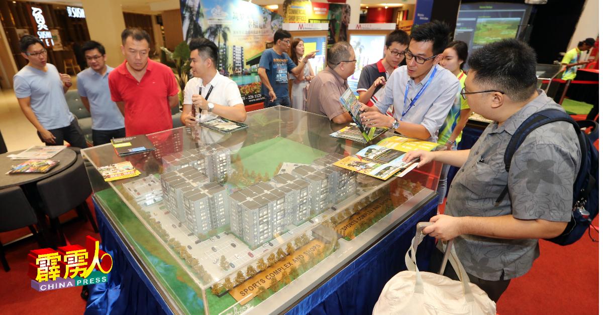 推介期间,民众也前往展销摊参观建筑模型。