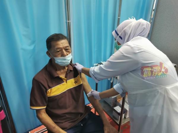护士为黄良武注射疫苗。