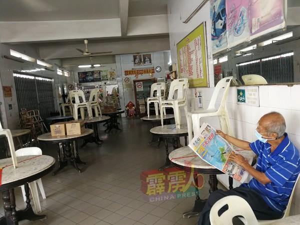 泰茶室唯一的帮工佳哥,在等候顾客光顾的闲暇时间,以阅报打发时间。