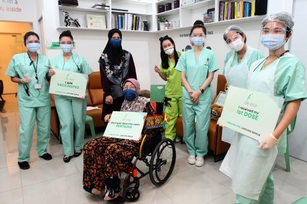 罗哈妮达(站者左3)陪同母亲(坐者)接种后,与医护人员分享喜悦。