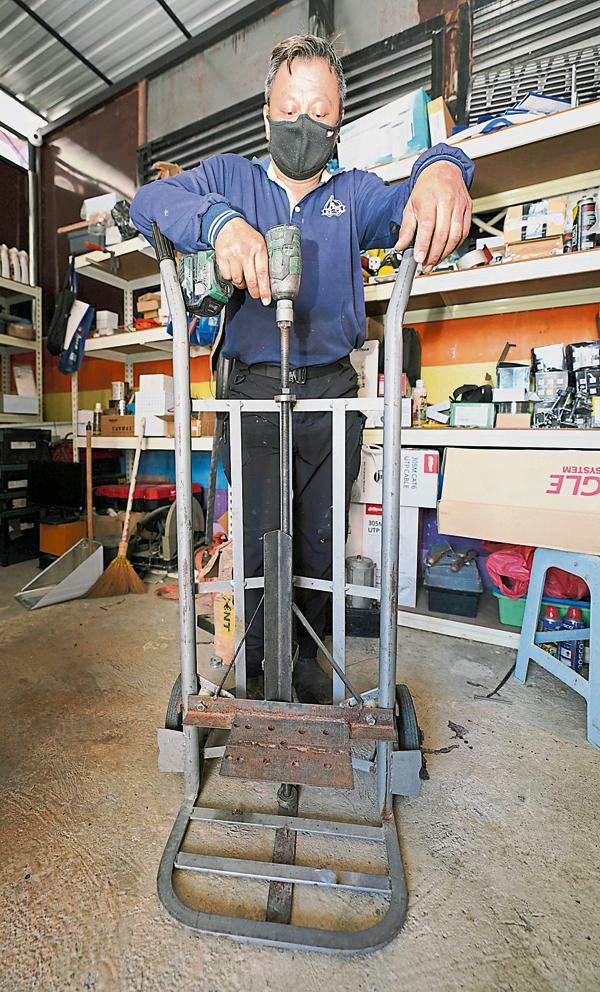 劳学伟将货运推车改良成一部可承受250公斤的起重机,辅助按装电动门的工作。