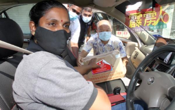 女司机从谢保恒(右)手中接获粮食箱。