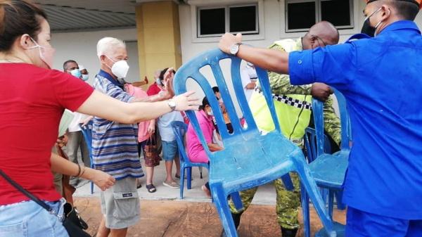 民众向工作人员索讨椅子,让长者坐着等候。