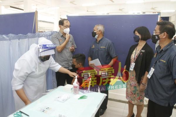 马汉顺(站者左2起)在米奥和冯碧仪陪同下,巡视学校疫苗接种中心。