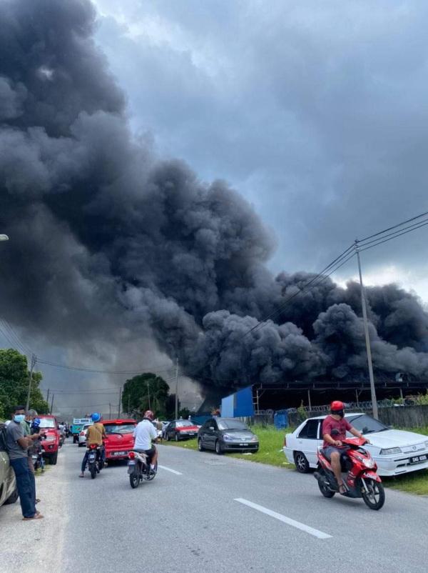 在易燃物助威下,失火工厂冒出浓浓乌烟。