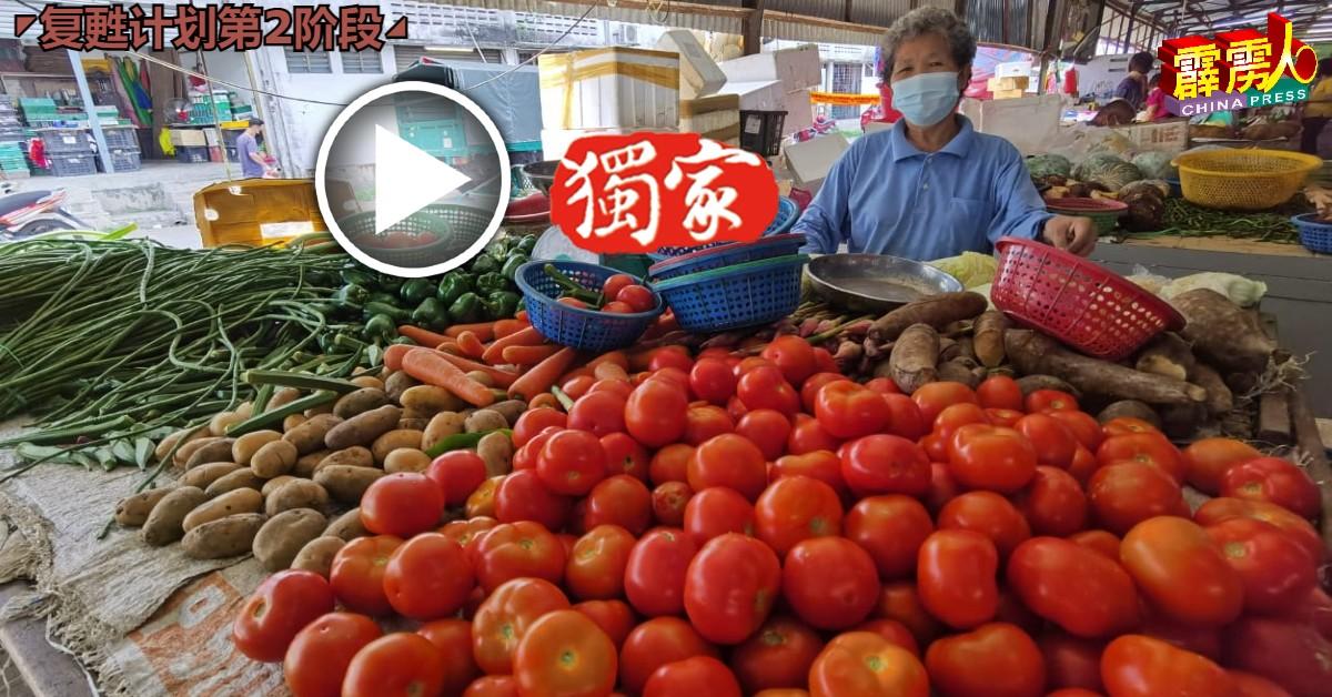 黄瑞兰对着未卖完的满摊蔬菜发愁。